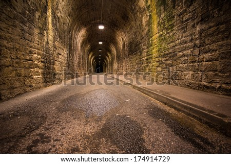 Old vintage tunnel in Biarritz at night. Lo,g time exposure. Old bricks and humidity on the ground. - stock photo