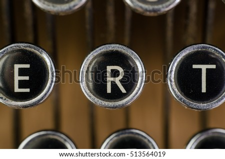 Old vintage typewriter on wooden desk. close up of black and white keys focusing on the letter R.