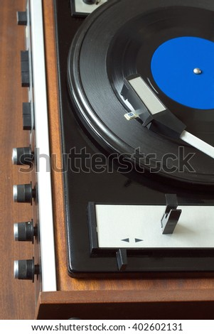 Old vintage vinyl record player in brown wooden case playing LP record with blue label. Top view vertical photo closeup - stock photo