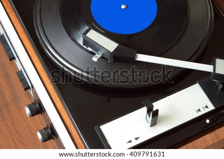 Old vintage vinyl record player in brown wooden case playing LP record with blue label. Top view horizontal photo closeup - stock photo