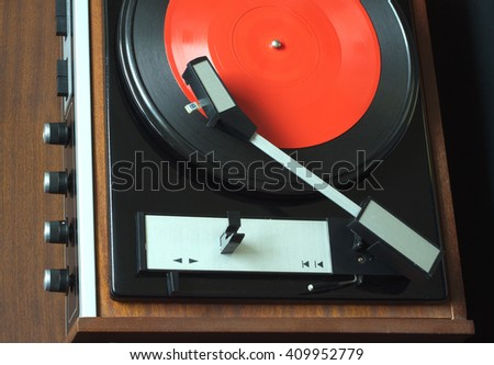 Old vintage vinyl record player in brown wooden case playing red flexible LP record. Top view horizontal photo closeup - stock photo