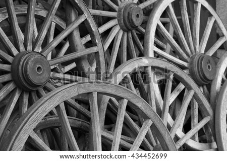 Old vintage wagon wheels stacked over each other, in black and white - stock photo