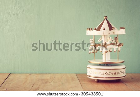 old vintage white carousel horses on wooden table. retro filtered image  - stock photo
