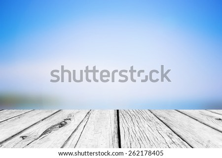old vintage wooden desk table with blurred sea and blue sky  backgrounds - stock photo