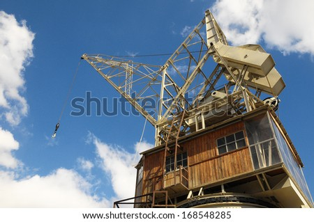 Old Vintage Wooden Port Crane on a Blue Sky