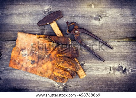 Old vintage working tools. Hammer, pliers, rusty nails and gloves on wooden background. Cross process look. - stock photo