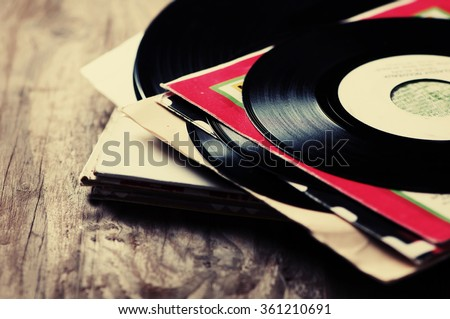 old vinyl record on the wooden table, selective focus and toned image - stock photo