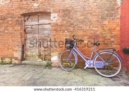 old violet bicycle parked long an external wall in Burano island, Venice