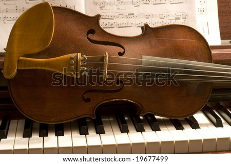 Old violin lying on a piano keyboard with sheet music behind - stock photo