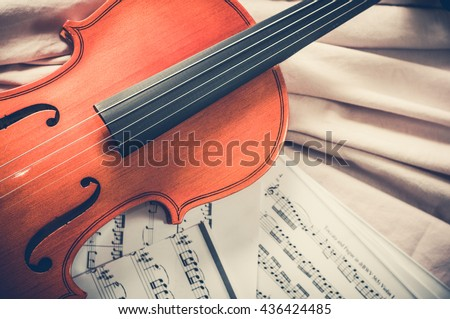 Old violin lying on the sheet of music, music concept. - stock photo