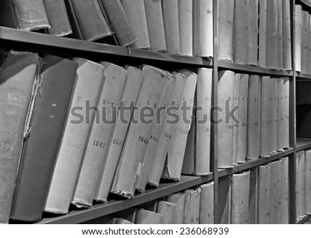 Old volume of library books on shelving - stock photo