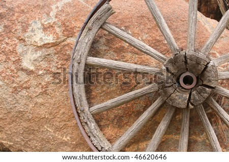 Old Wagon Wheel Against Rock - stock photo