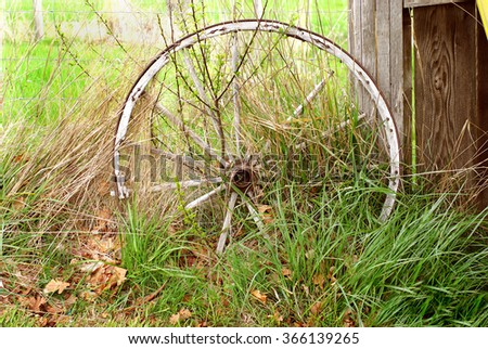 old wagon wheel in abandoned farm fence with overgrown grass and weathered wood - stock photo