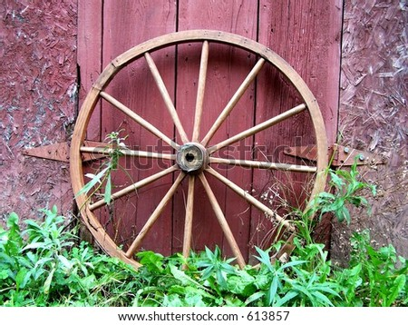 Old wagon wheel leaning on a barn. - stock photo