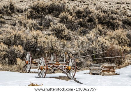 Old wagon with rusty metal and weathered wood parts retired to Bannack State Park in Montana