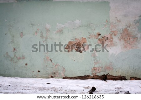 Old wall and a ground covered with snow - stock photo
