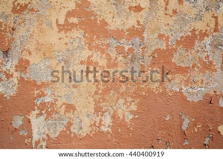 Old wall background Damaged plaster,orange painted cracked wall - stock photo