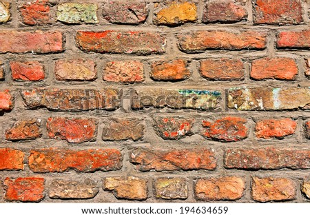 Old wall built from red bricks collected in different places - stock photo
