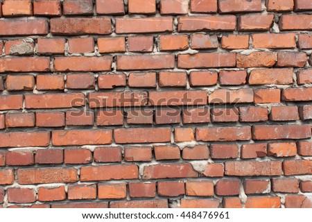 Old wall from red brick. Red clay brick. Brick wall. The old crumbling brick wall. Bricks and stones in the old wall. The old brick wall collapses and urgent repair is necessary. - stock photo