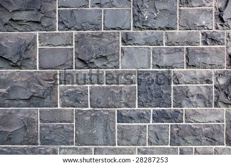 Old wall of bluestone blocks.  This stone is common in early buildings in Melbourne, Australia. - stock photo