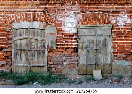 Old wall of red brick with two closed windows. - stock photo