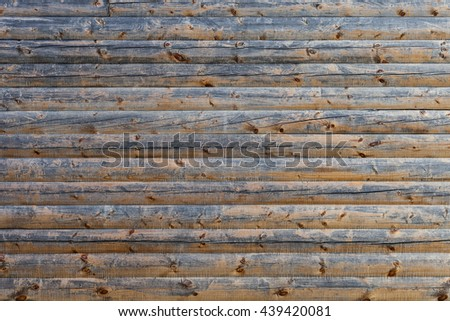 Old wall of wooden planks with cracks. Beam made of wood to build a house. Old shabby wall or fence paneling