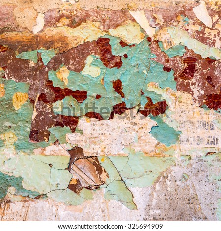 Old wall texture - peeling teal and maroon paint, some plaster and tattered newspaper (fragments of sentences and words written in Russian) - stock photo