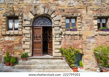Old wall with arched wooden door and windows, Siena, Italy. - stock photo