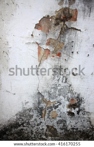 Old wall with cracks and peeling paint. Old lime whitewash. Background. Texture. The wall needs repair. Decorative facade.