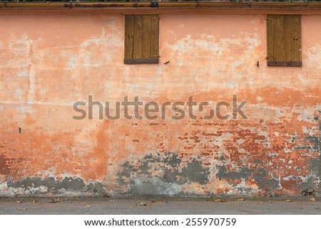 old wall with peeling paint, scratched stained plaster and closed windows - grunge background of urban decay   - stock photo