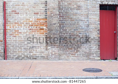 old wall with red door brick sidewalk background - stock photo