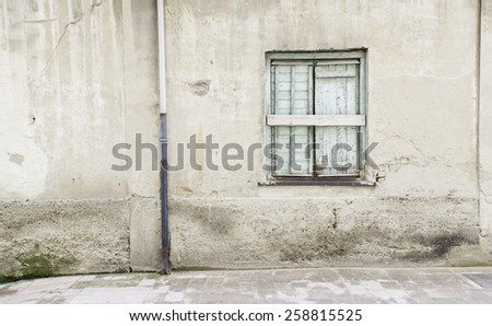 Old wall with window detail of an old building in ruins - stock photo