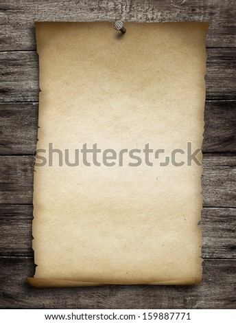 old wanted paper or parchment pinned by nail to grunge wooden background - stock photo