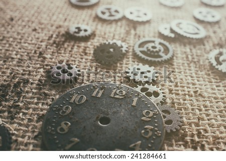 Old watch face surrounded by parts. - stock photo