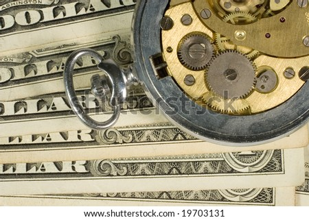 Old watch mechanism and dollar bills (time is money concept)