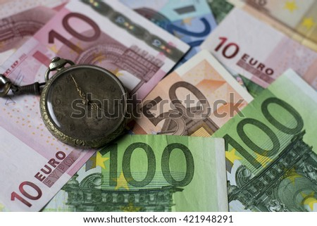 Old watch with euro banknotes