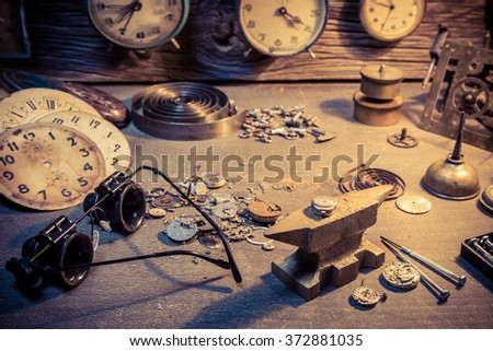 Old watchmaker's workshop with parts of clocks - stock photo