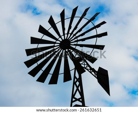 Old water pumping windmill. Windmill water tower on sky background. Dark silhouette of farm windmill. - stock photo