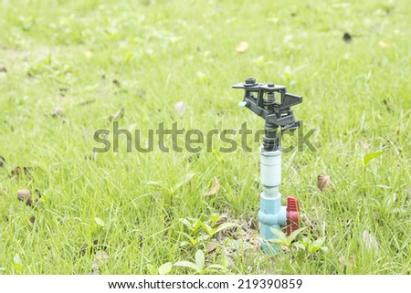 Old water sprinkler on the green lawn - stock photo