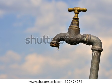 Old water tap with dripping water - stock photo