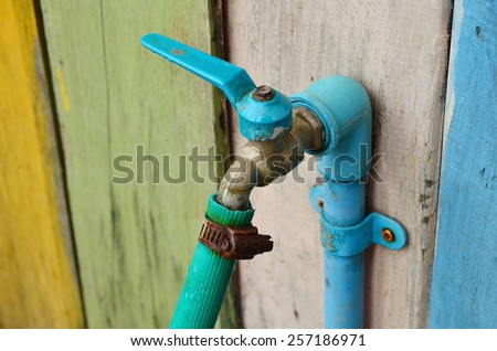 Old water tap with rubber tube on colorful wooden wall. - stock photo