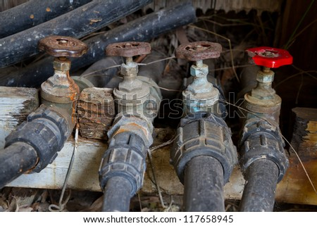 Old water taps and valves on irrigation pipes - stock photo