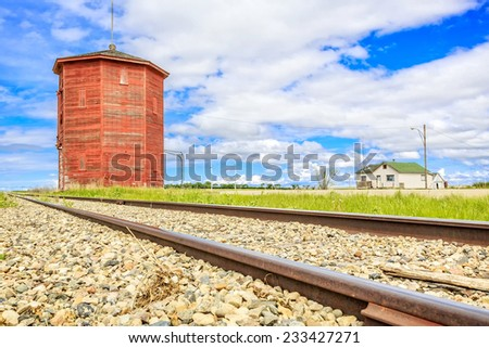 Old water tower or station along the railroad track on the prairies. - stock photo
