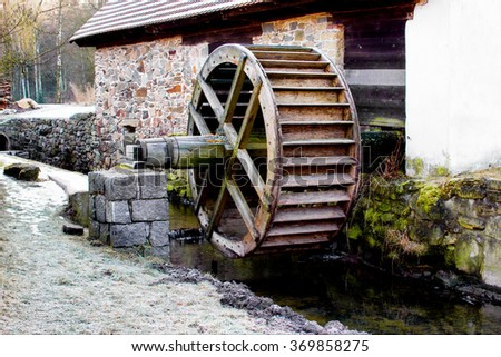 old water wheel in stream by historic steelworks