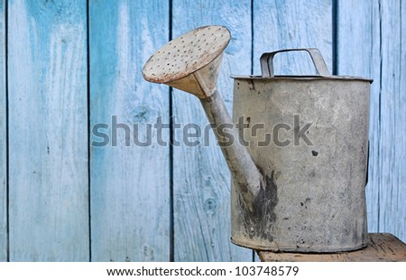 old watering can on wooden background - stock photo