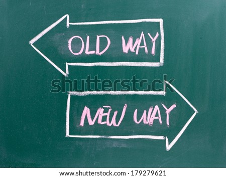 Old Way, New Way written on a blackboard with arrows pointing in the direction of the past and the future. A concept for adapting to change, improvement and development for the self or the business  - stock photo