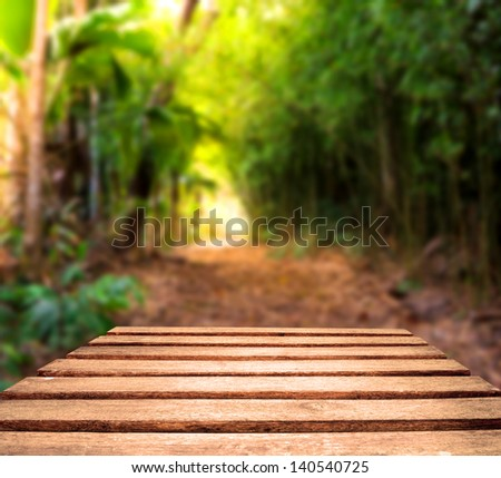 Old weather worn plank table top with tropical jungle path in background.  Focus is on planks in foreground
