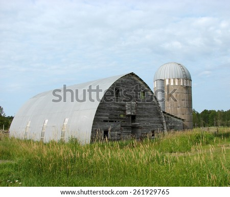 old weathered abandoned farm building barn and silo - stock photo