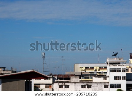 old weathered aluminum TV antenna on an old house roof top silhouette with blue sky background - stock photo