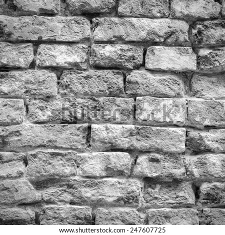 Old weathered and battered brick wall texture in black and white tone - stock photo